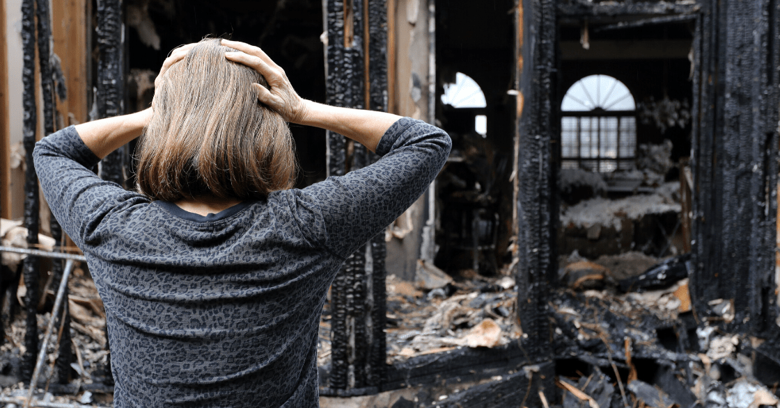 Woman looking at burned home